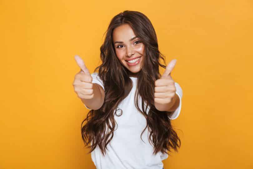 Mulher jovem feliz isolada sobre fundo amarelo, mostrando os polegares para cima gesto.