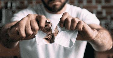 Um homem rasgando, no meio, uma foto de sua ex-namorada.