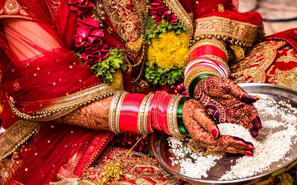 Noiva hindu indiana vestindo uma linda Lehenga vermelha em seu casamento e realizando o ritual tradicional de oferecer arroz a Deus com ambas as mãos