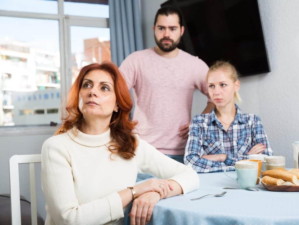 Uma mulher sentada à mesa olhando pra cima. Ao fundo, uma mulher e um homem. Todos eles com semblante de evidente desconforto.