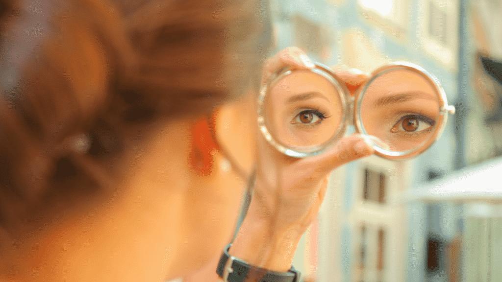 Mulher observando reflexo do seus olhos em espelho de maquiagem
