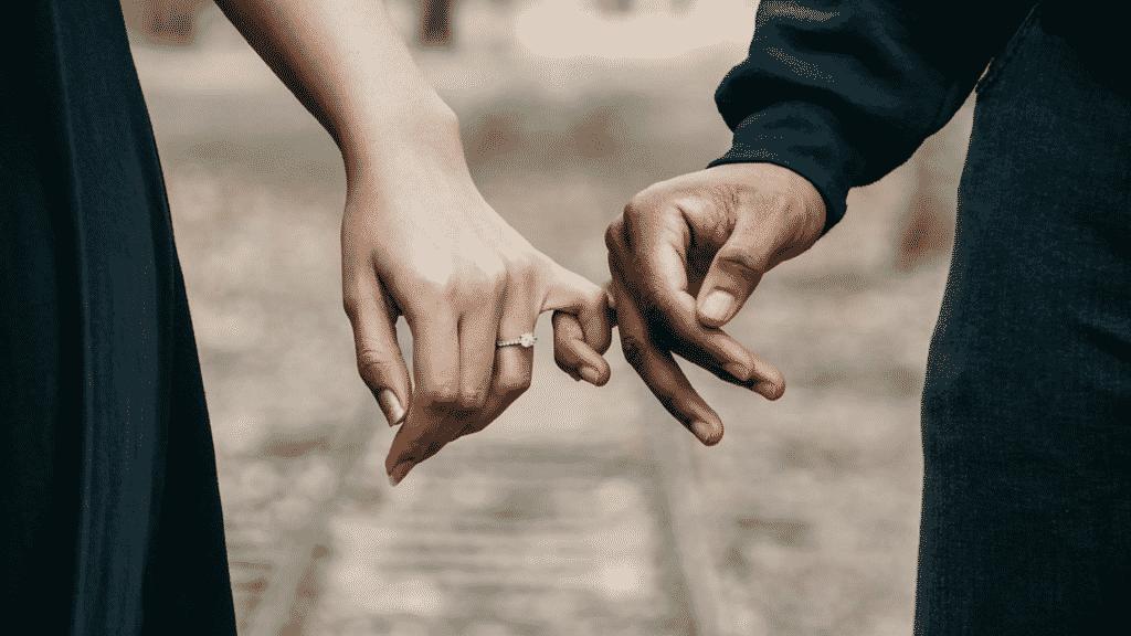 Casal de mãos dadas caminhando na rua