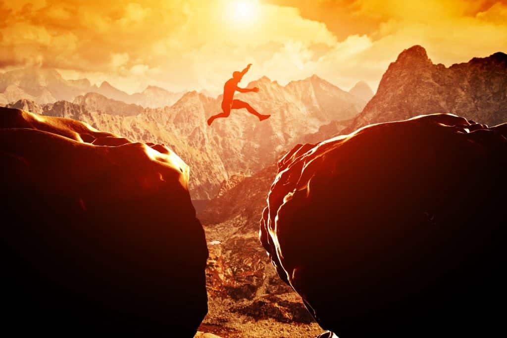 Desenho de um homem pulando de uma montanha para outra.