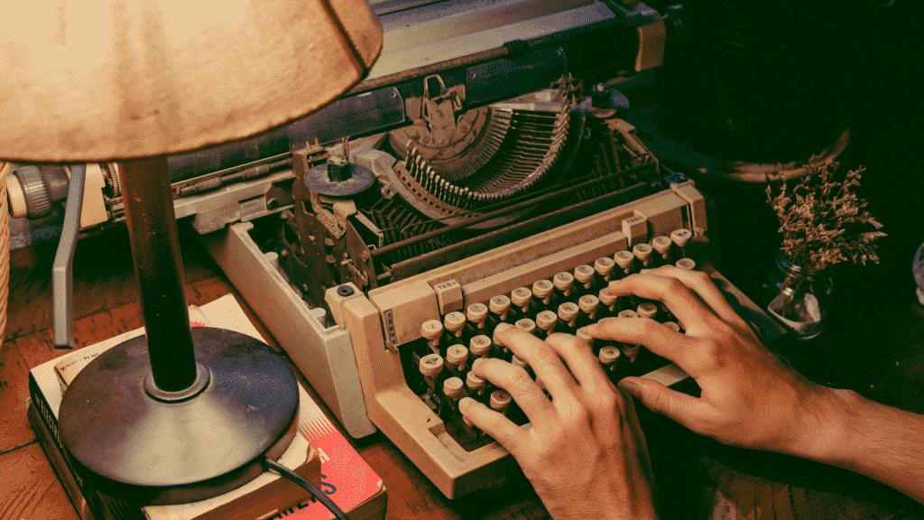 Homem escrevendo na máquina de datilografia