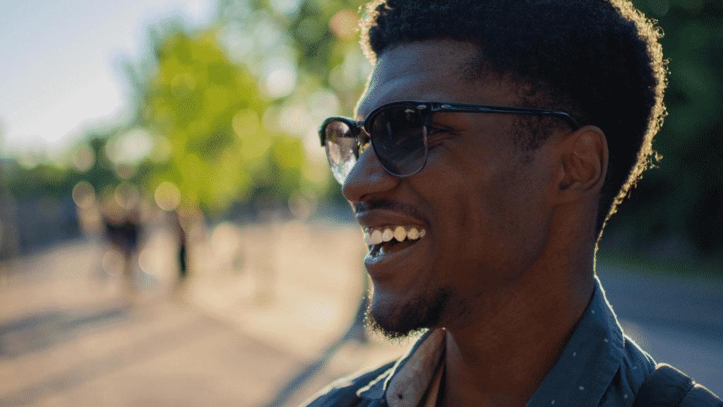 Homem sorridente usando óculos de sol