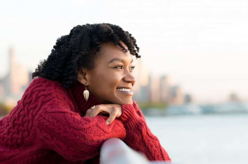 Mulher negra sorrindo olhando o horizonte.