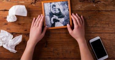 Mulher irreconhecível segurando foto quebrada de casal apaixonado. Relacionamento encerrado.