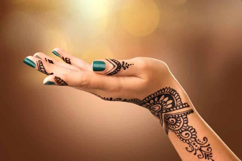 Mão de uma mulher com tatuagem mehndi.
