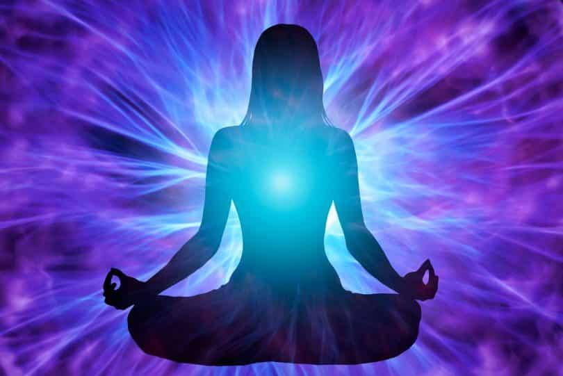 Silhueta de mulher meditando com energias ao redor.