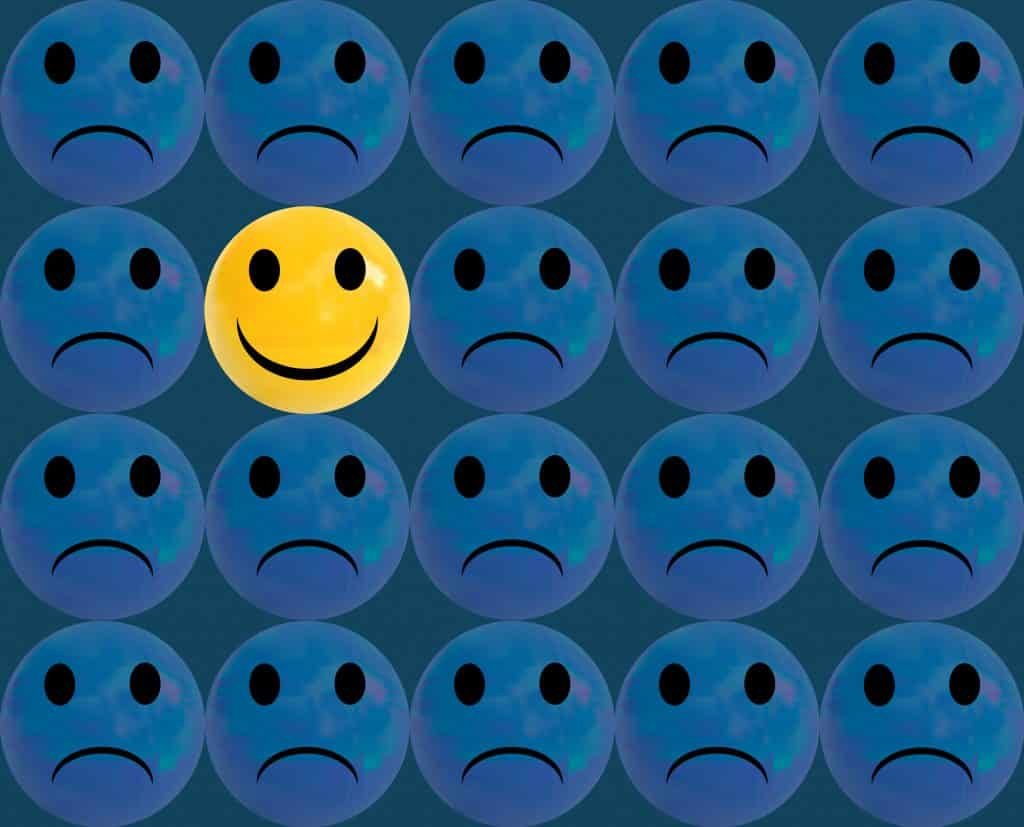 Ilustração de rostos tristes com um rosto feliz no meio