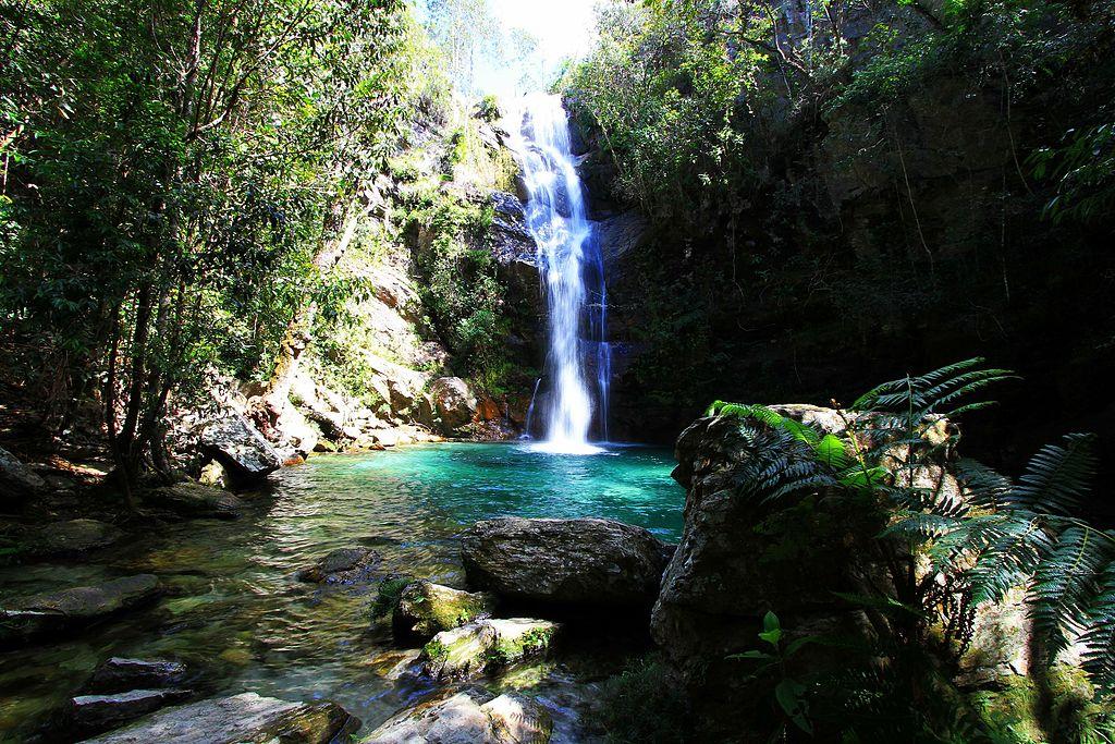 Uma pequena cachoeira ao fundo. Embaixo dela, uma água de coloração azulina muito forte. Em primeiro plano, pedras e árvores.