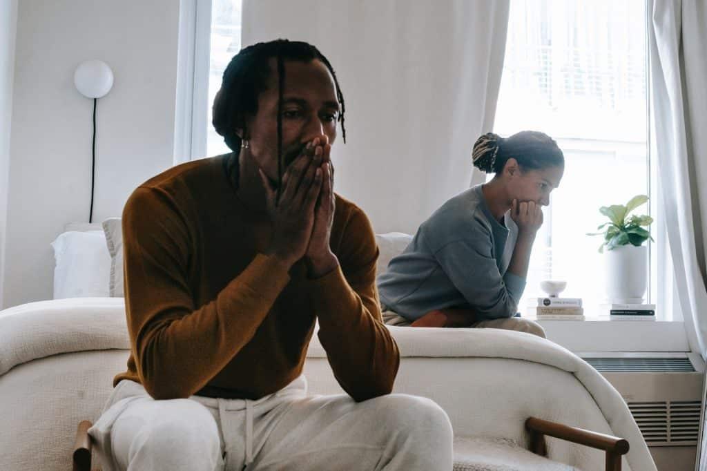 Em primeiro plano, um homem sentado próximo à uma cama. Ele está com as mãos sobre o rosto. Em plano secundário, uma mulher sentada numa cama, pensativa.