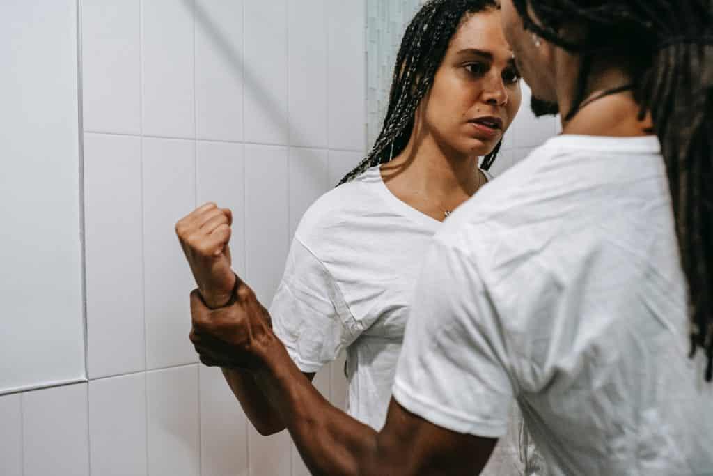 Uma mulher negra em plano posterior e, em plano primeiro, um homem negro segurando o braço da primeira.