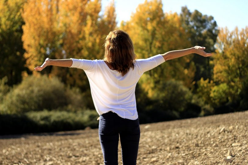 Uma mulher de camiseta branca e calça jeans abrindo e erguendo os braços. Ao fundo, um local repleto de árvores.