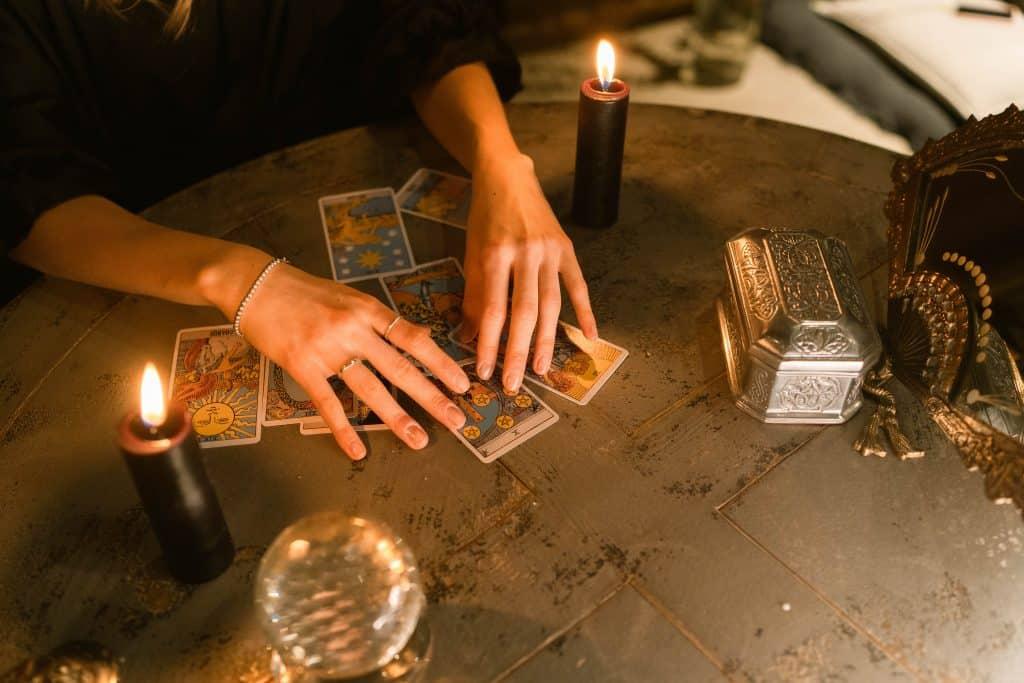 Mãos de uma mulher manipulando um baralho de cartas. Sobre uma mesa, uma vela preta acesa e um leque de ferro, além de um globo cinza e também uma caixa acinzentada.