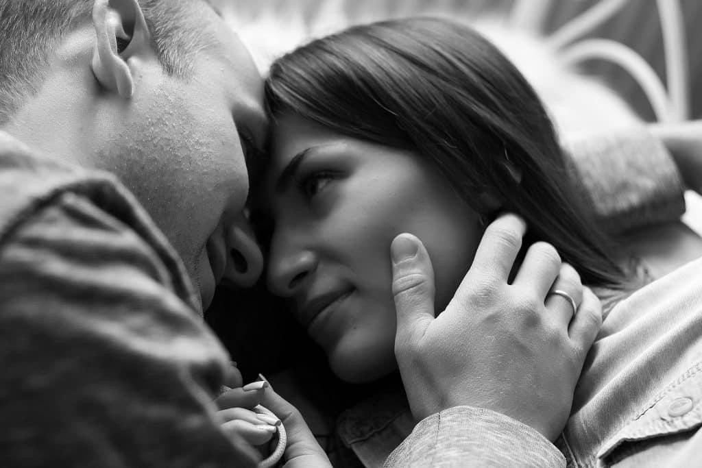 Um homem e uma mulher se olhando. O homem coloca sua mão direita sobre o rosto da mulher.