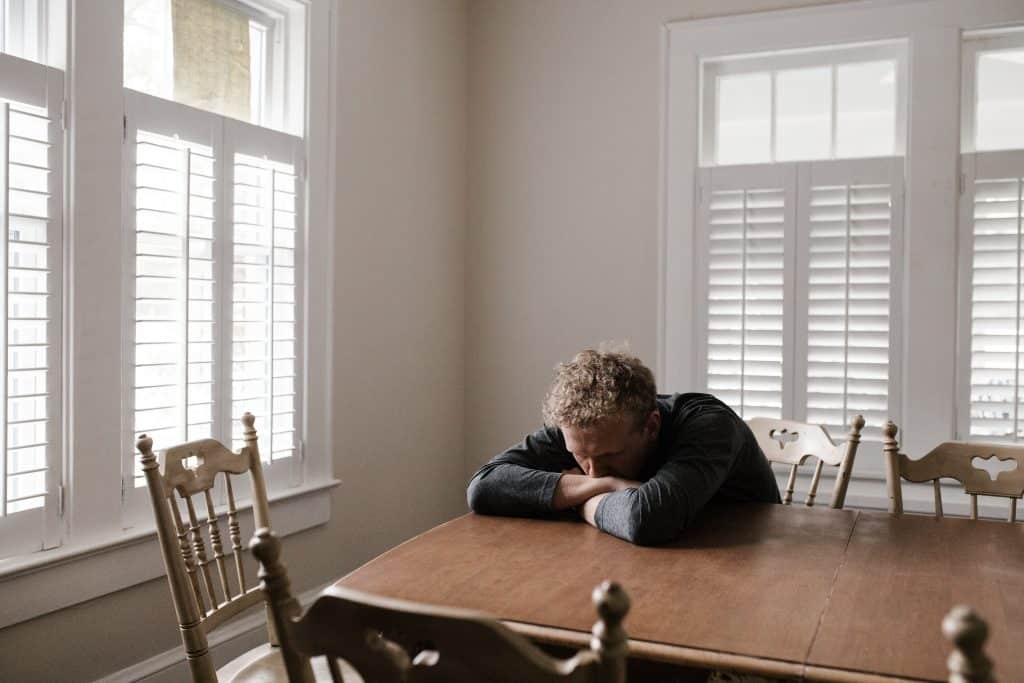 Um homem branco sentado, debruçando sua cabeça sobre uma mesa. Ao fundo, uma sala com janelas à esquerda e à direita.