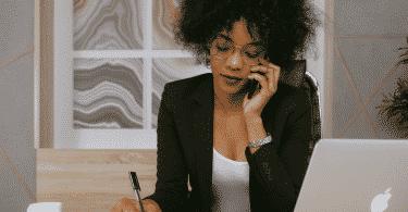 Uma mulher trajada de roupa social falando ao telefone.