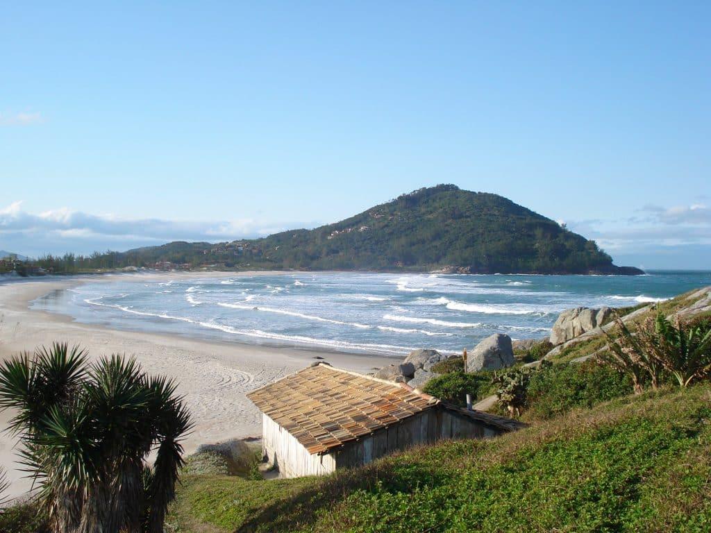 Praia da Ferrugem: uma praia, entornada por uma sutil região montanhosa esverdeada. Em primeiro plano, uma casa e um declive com grama verde.
