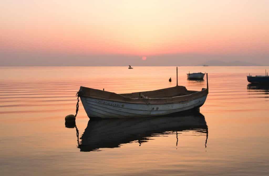 Um barco pequeno de coloração branco no meio de um rio. Ao fundo, outros barcos. Há também um pôr-do-sol.