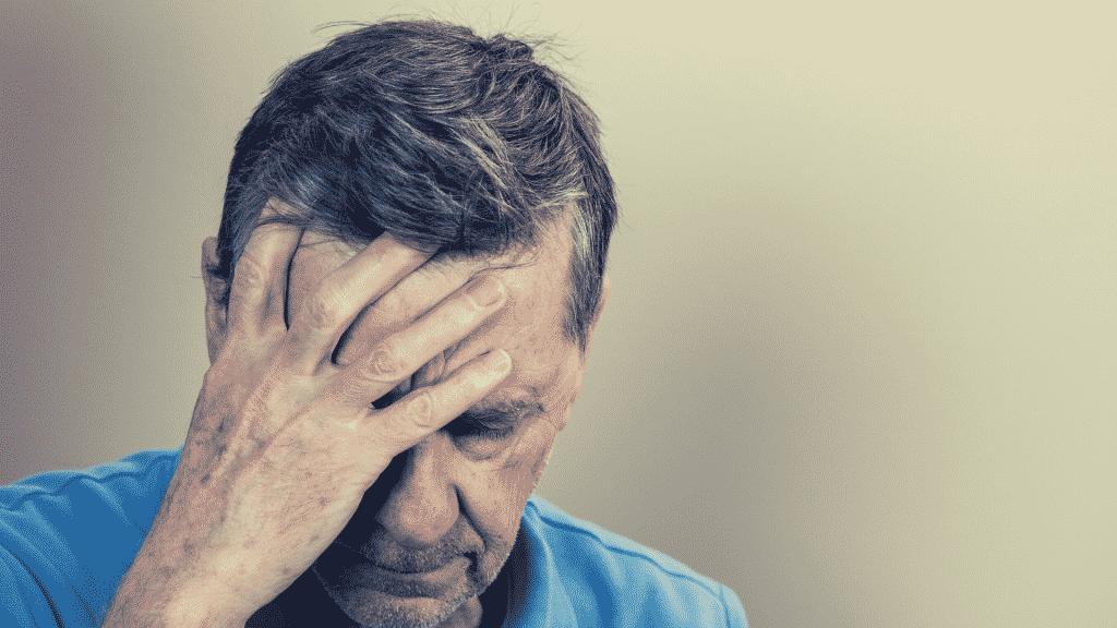 Um homem com expressão de desconforto colocando sua mão direita sobre o rosto.