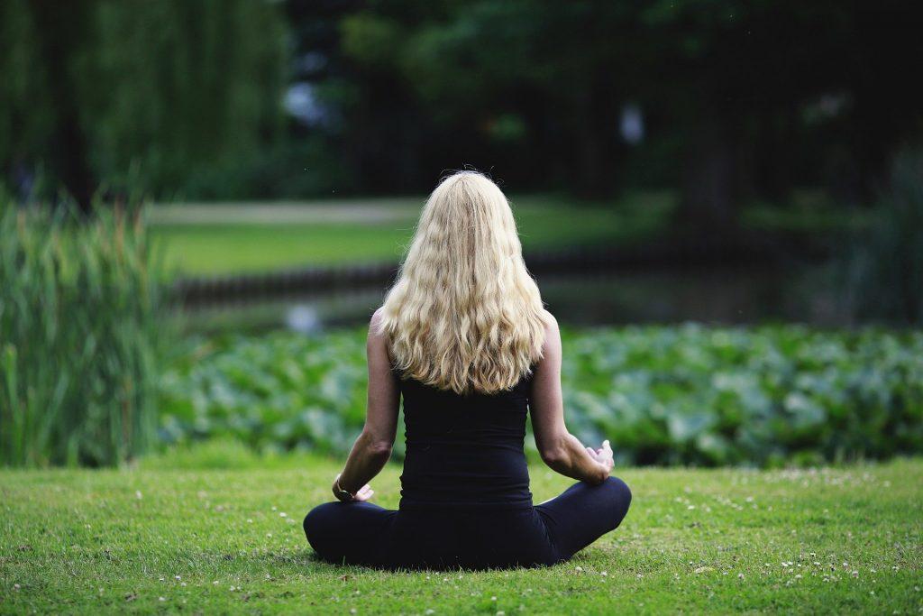 Uma mulher meditando num parque repleto de zonas verdes. Ao fundo, desfocado, um lago.