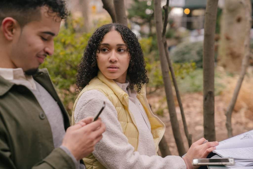 Um homem sorridente mexendo num celular e uma mulher olhando pra ele, aflitiva.