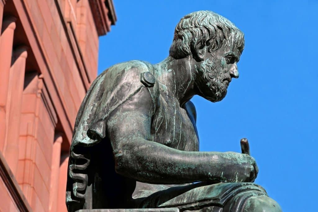 Uma estátua de Aristóteles. Ao fundo, uma edificação de coloração vermelha, situada à esquerda da estátua.