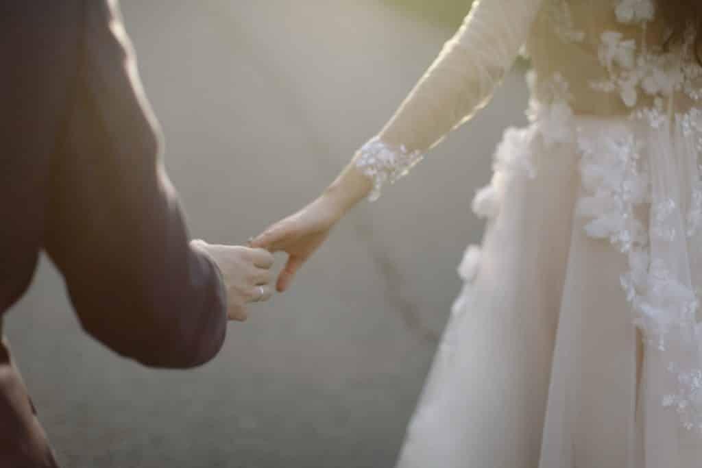 Uma mulher, à direita, vestida com um vestido de noiva e, à esquerda, um homem de terno e uma aliança. Ambos estão dando as mãos um ao outro.
