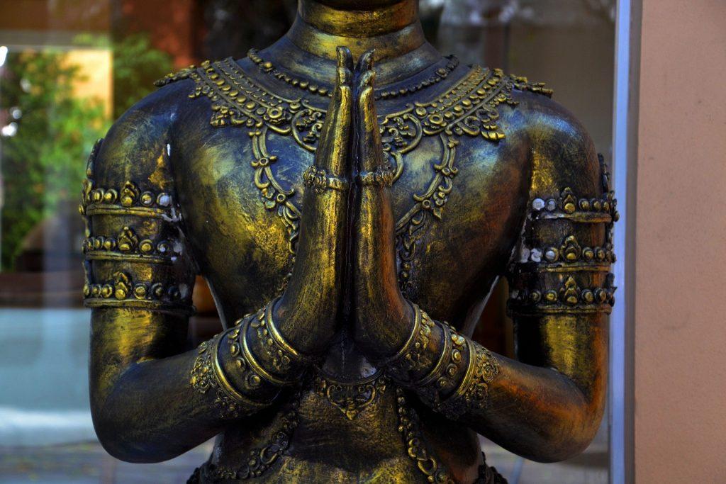 Uma estátua budista em bronze. Ela cerra as mãos em um gesto de oração.