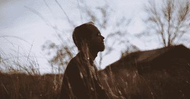 Homem sentado de olhos fechados no meio de um campo, meditando