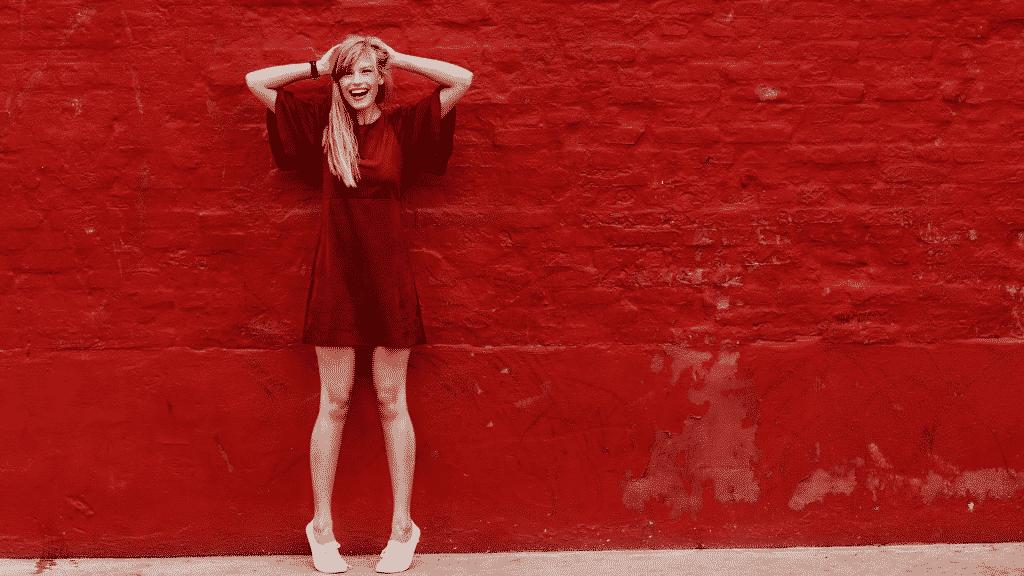 Mulher sorrindo de vestido vermelho, encostada em uma parede pintada de vermelho
