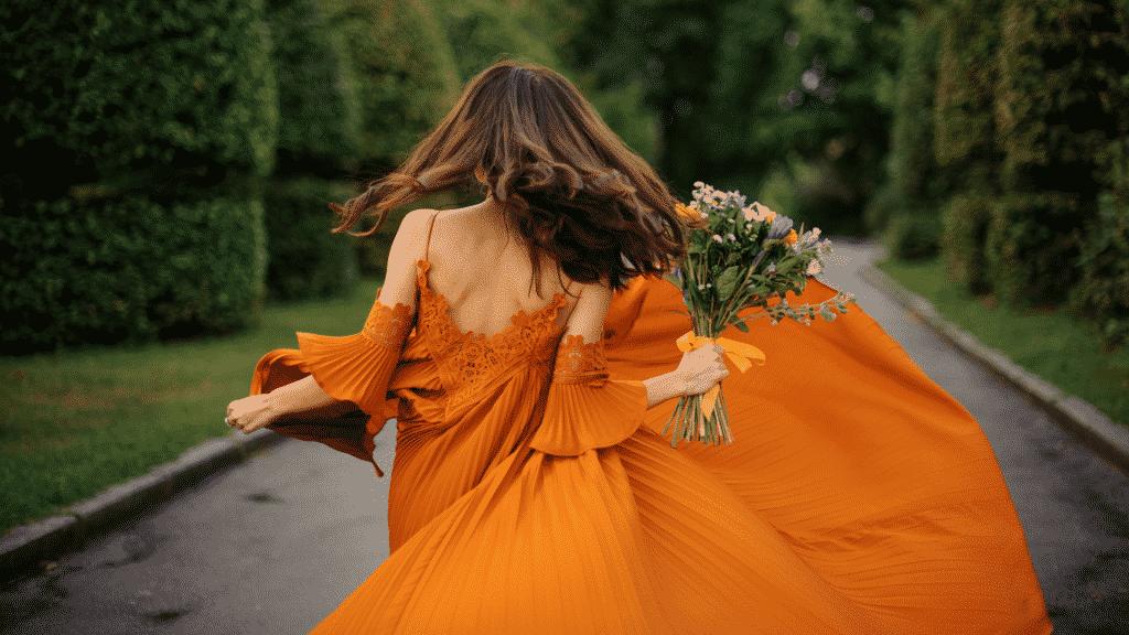 Mulher usando um longo vestido laranja e segurando um buquê de flores, de costas para a foto