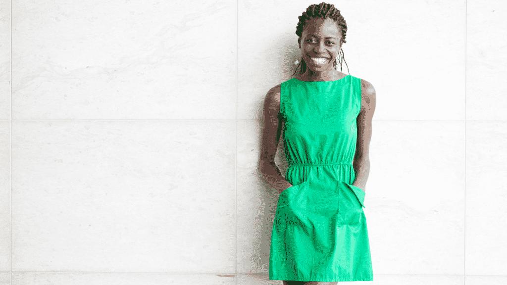 Mulher sorrindo com as mãos nos bolsos de um vestido verde