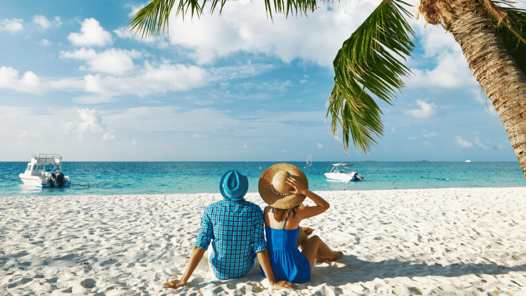 Casal com roupas azuis, sentados na areia de frente para o mar