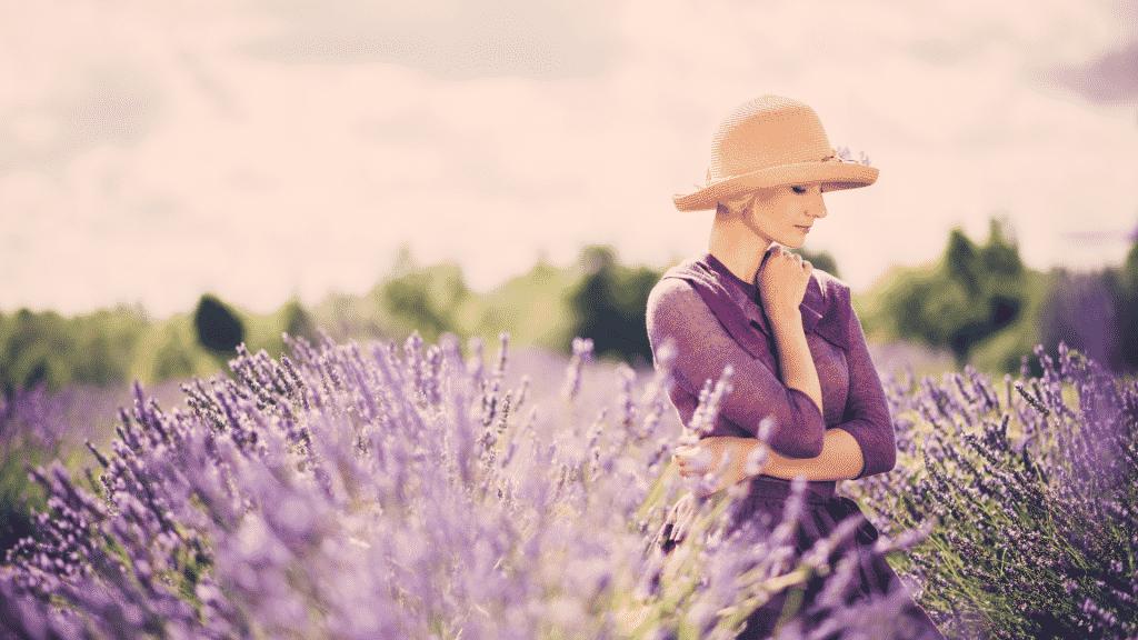 Mulher de chapéu e vestido roxo no meio de um campo com flores roxas