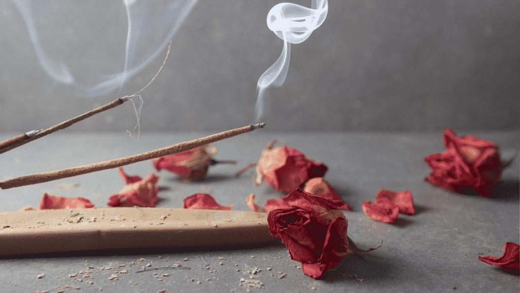 Incensos sendo queimados e pétalas de rosa sobre uma mesa