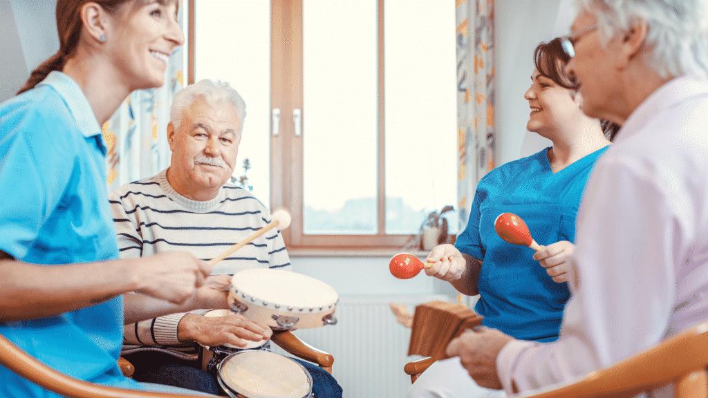 Terapeutas e idosos em uma roda tocando instrumentos musicais