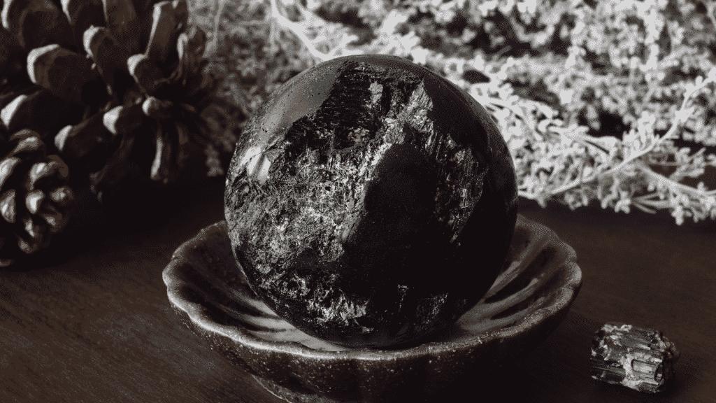 Imagem de uma Turmalina Negra em um recipiente, sobre uma mesa