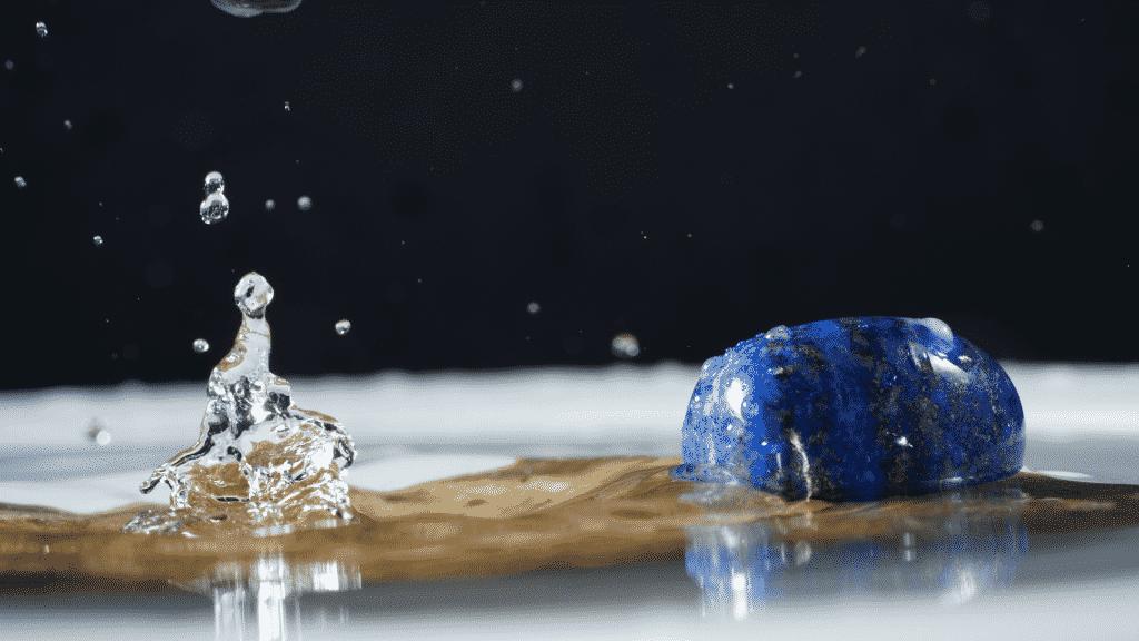 Imagem de uma pedra Lápis Lazúli sobre uma mesa molhada com água