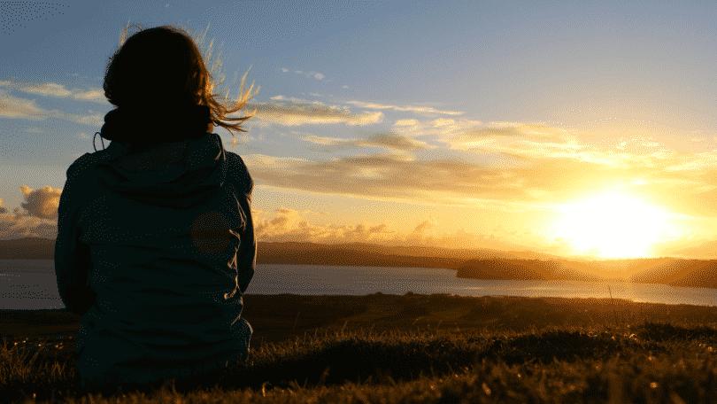Mulher sentada em um campo observando o sol