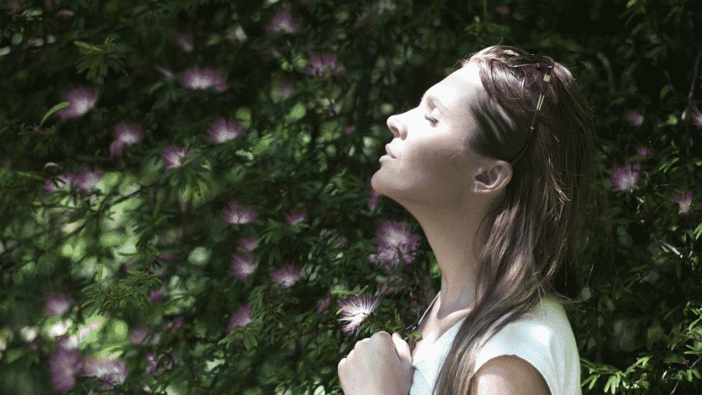 Mulher de olhos fechados em um jardim respirando ar puro