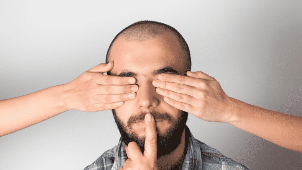 Homem com os olhos e a boca tapados pelas mãos de outras pessoas