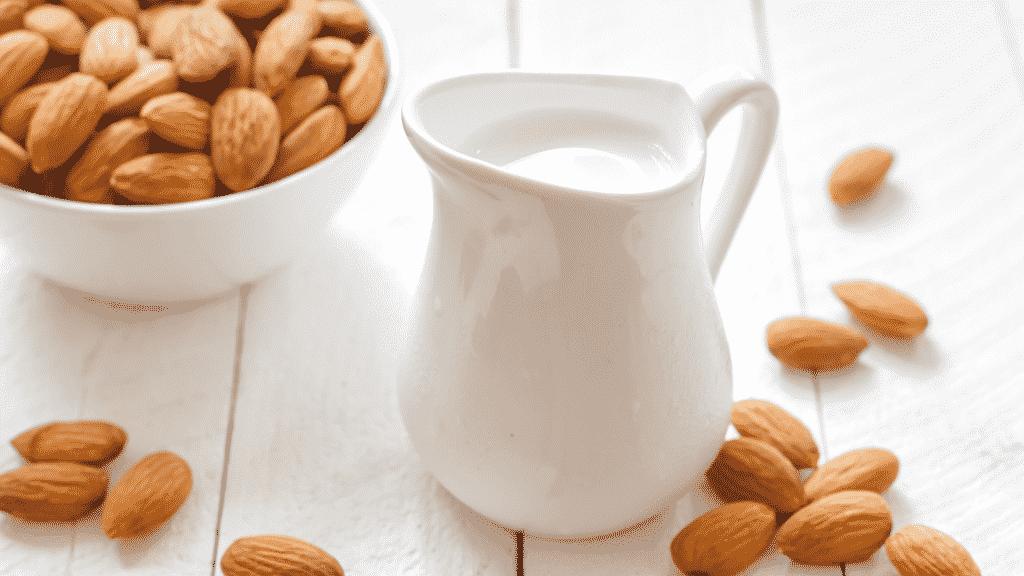 Leite de amêndoas em uma jarra. Ao redor  da jarra, diversas sementes de amêndoas pela mesa e em um recipiente