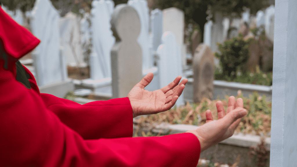 Pessoa fazendo uma prece em frente a um túmulo