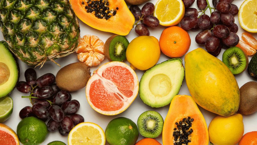 Diversas frutas inteiras e cortadas em cima de uma mesa branca