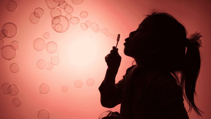 Silhueta de uma criança brincando com bolhas de sabão