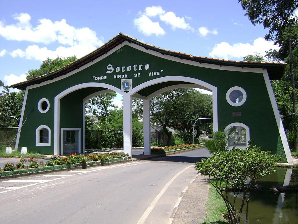 """Entrada do município de Socorro. Num letreiro está escrito """"Socorro"""" e no debaixo """"onde ainda se vive""""."""