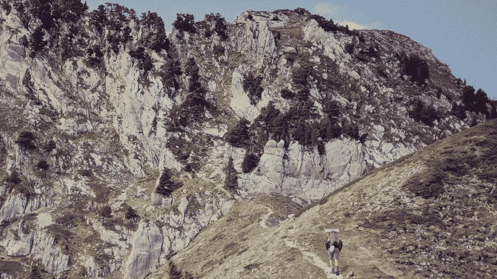 Uma pessoa fazendo uma escalada rumo à uma montanha.