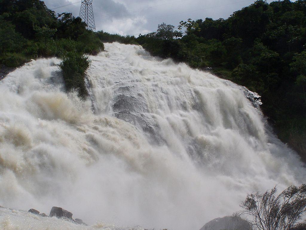 Uma cachoeira/cascata intensa. Acima dela, uma zona verde repleta de mato e árvores.